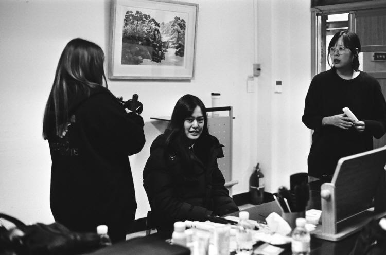 영화 '최선의 삶' 영화 촬영 중 자리에 앉아 있는 한성민 배우(연소영 역)가 카메라를 쳐다보고 있고, 그녀의 왼쪽에는 헤어스타일리스트가, 오른쪽에는 이우정 감독이 서 있다. 이 사진은 흑백으로 되어 있다.