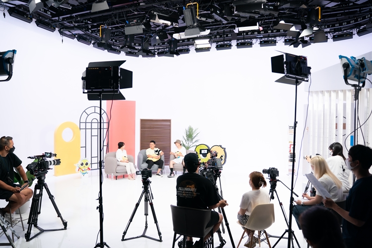 촬영이 한창 중인 녹화 현장의 모습. 천장에 조명이 달려있고, 녹화장 가운데 놓인 회색 1인용 쇼파 3개에 각각 출연진들이 앉아있다. 출연진 앞에는 스태프들이 있고, 조명이 놓여있다.