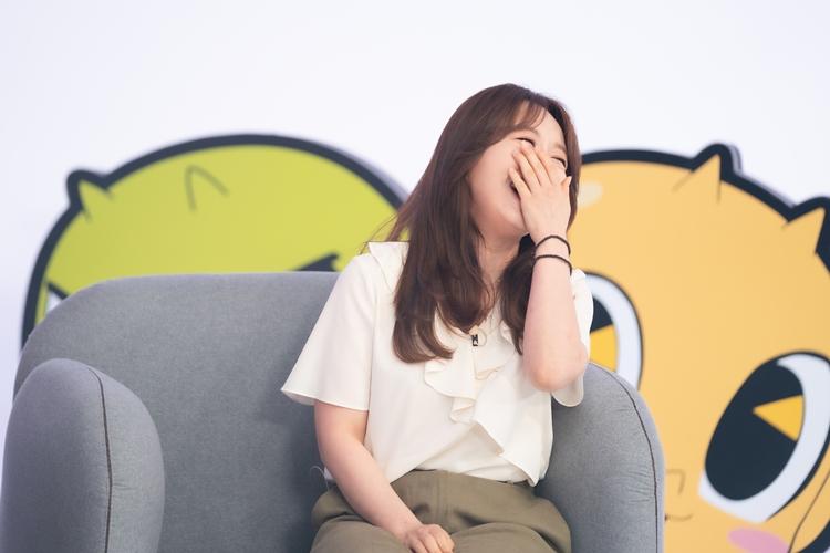 신비, 금비 판넬을 배경으로 회색 쇼파에 성우 조현정 님이 앉아 입을 손으로 가리며 웃고 있는 모습.