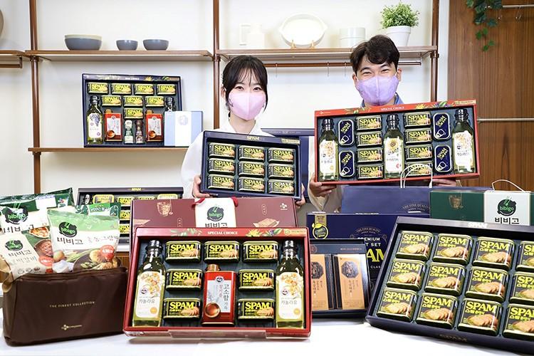 스팸 선물세트를 포함한 8개의 CJ제일제당 선물세트가 테이블 위에 놓여져 있고, 여성 남성 모델이 각각 다른 스팸 선물세트를 들고 마스크를 쓴 채 미소를 짓고 있다.