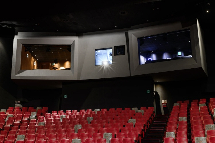 CGV용산아이파크몰 스카이박스 내부 전경으로 상단 중앙엔 영상실이 양 옆엔 각기 다른 조명색이 빛나는 스카이 박스 모습이, 그리고 하단엔 일반 좌석 모습이 보인다.