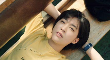 노란색 티셔츠를 입은 미래가 벤치에 누워 하늘을 바라보며 엄마가 될 미래에 대해 상상을 하고 있다.