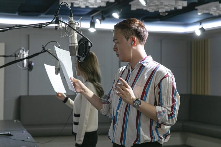 김동현 님이 마이크 앞에서 왼쪽 귀에 이어폰을 끼고, 오른 손에 대본을 들고 연기를 하고 있는 모습.
